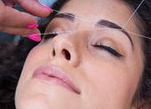 Kvinna på ansikts hårborttagning threading förfarande — Stockfoto