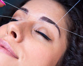 η γυναίκα του προσώπου αφαίρεση τρίχας πέρασμα κλωστής σε βελόνα διαδικασία — Φωτογραφία Αρχείου
