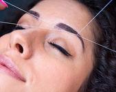Frau auf die gesichts-haarentfernung threading-verfahren — Stockfoto