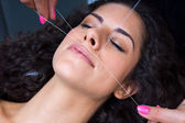 Woman on facial hair removal threading procedure — ストック写真