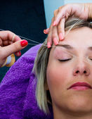 Threading hair removal procedure — Stock Photo