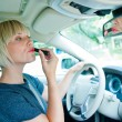 Attractive woman applying make up in her car — Stock Photo