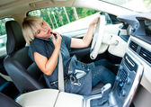 Attractive woman applying make up in her car and talking on mobi — Stok fotoğraf