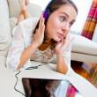 Attractive woman listen music on sofa — Stock Photo