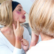 Woman covered with bruises in front of the mirror — Stock Photo