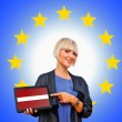 Woman holding tablet with latvian flag on european union backgr — Stock Photo #33920485