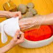 Woman foot in paraffin bath at the spa — Stock Photo #33925623