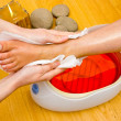 Woman foot in paraffin bath at the spa — Stock Photo #33925891