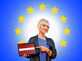 Woman holding tablet with latvian flag on european union backgr — Stock Photo
