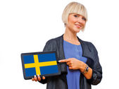 Attractive blond woman holding tablet with sweden flag — Stock Photo