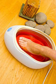 Woman foot in paraffin bath at the spa — Stock Photo