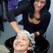 Hairdresser washing woman hair — Stock Photo