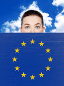 Woman face behind wall with european union flag — Stock Photo