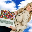 Attractive woman holding laptop with world flags — Stock Photo