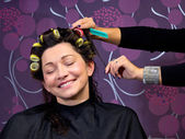 Hairdresser putting rollers in woman hair — Stock Photo