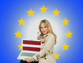 Woman holding laptop with latvian flag — Stock Photo
