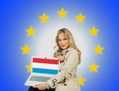 Woman holding laptop with luxembourgh flag — Stock Photo