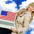 Attractive woman holding laptop with usa flag — ストック写真