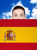 Woman face behind wall with spain flag — Stock Photo
