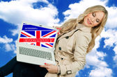 Attractive woman holding laptop with english language sign — Stock Photo