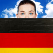 Woman face behind wall with german flag — Stock Photo
