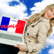 Woman holding laptop with french language sign — Stock Photo