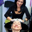 Hairdresser washing woman hair — Stock fotografie