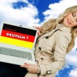 Stock Photo: Woman holding laptop with german language sign