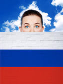 Woman face behind wall with russia flag — Stock Photo
