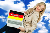 Woman holding laptop with german language sign — Stock Photo