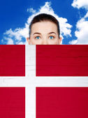 Woman face behind wall with denmark flag — Stock Photo