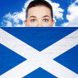 Woman face behind wall with scotland flag — Stock Photo #34901641