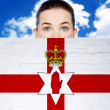 Woman face behind wall with northern ireland flag — Stock Photo