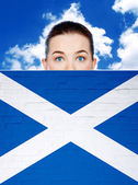 Woman face behind wall with scotland flag — Stock Photo