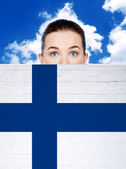 Woman face behind wall with finland flag — Stock Photo