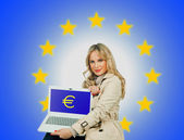 Attractive woman holding laptop with euro sign on the screen — Stock Photo
