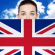 Woman face behind wall with UK flag — Stock Photo
