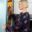Woman near fridge at home — Stock Photo