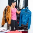 Attractive woman in front of closet full of clothes — Stock Photo #39346379