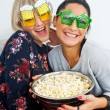 Stock Photo: Two attractive womfriends with funny glasses and popcorn