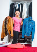 Attractive woman in front of closet full of clothes — Stock Photo