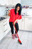 Attractive woman cleaning broken glass in kitchen — Stock Photo