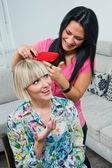 Woman combing friends hair — Stock Photo