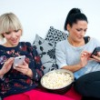 Two attractive woman friends with mobile phone and popcorn — Stock Photo