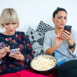 Two attractive womfriends with mobile phone and popcorn — Stock Photo #39350339