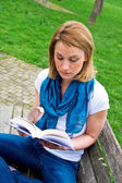 Attractive woman on the bench with book — Stock Photo