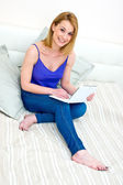 Woman with laptop in her bed — Stock Photo
