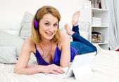 Woman in bed with laptop computer and headphones — Foto de Stock