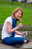 Attractive woman with laptop on park bench — Stock Photo