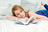 Woman reading book in bed — Stock Photo